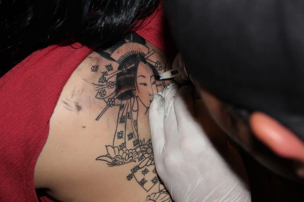 Ein Tattooartist arbeitet an einem Geishatattoo