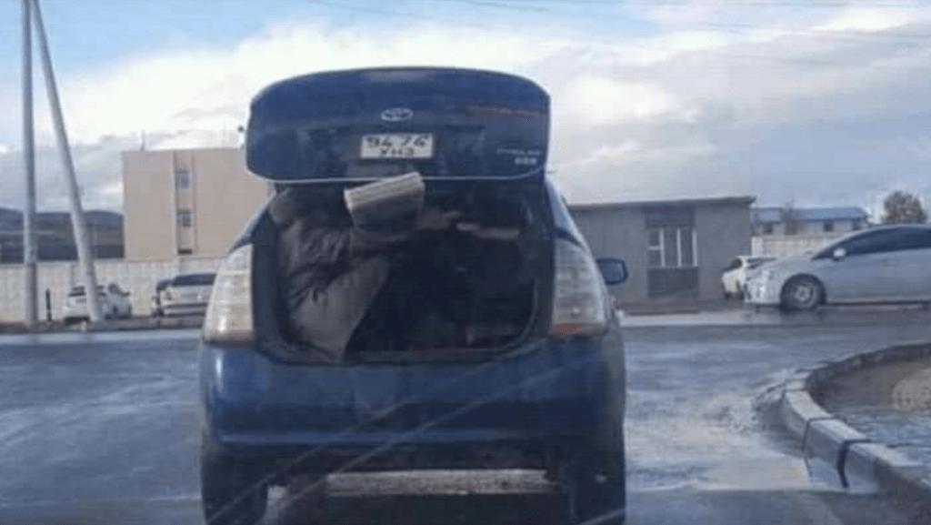 Only in Mongolia 16: Ein Mitfahrer hält eine Holzplanke fest auf der Fahrt