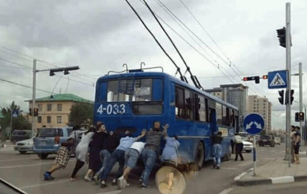 Menschen schieben einen Oberleitungsbus in der Mongolei an