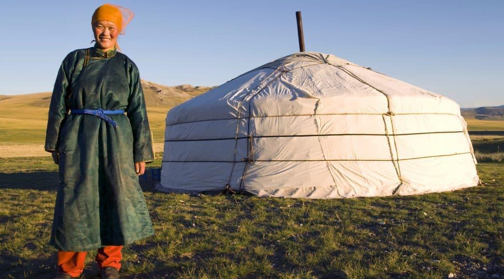 Frau in mongolischer Kleidung vor einer Jurte